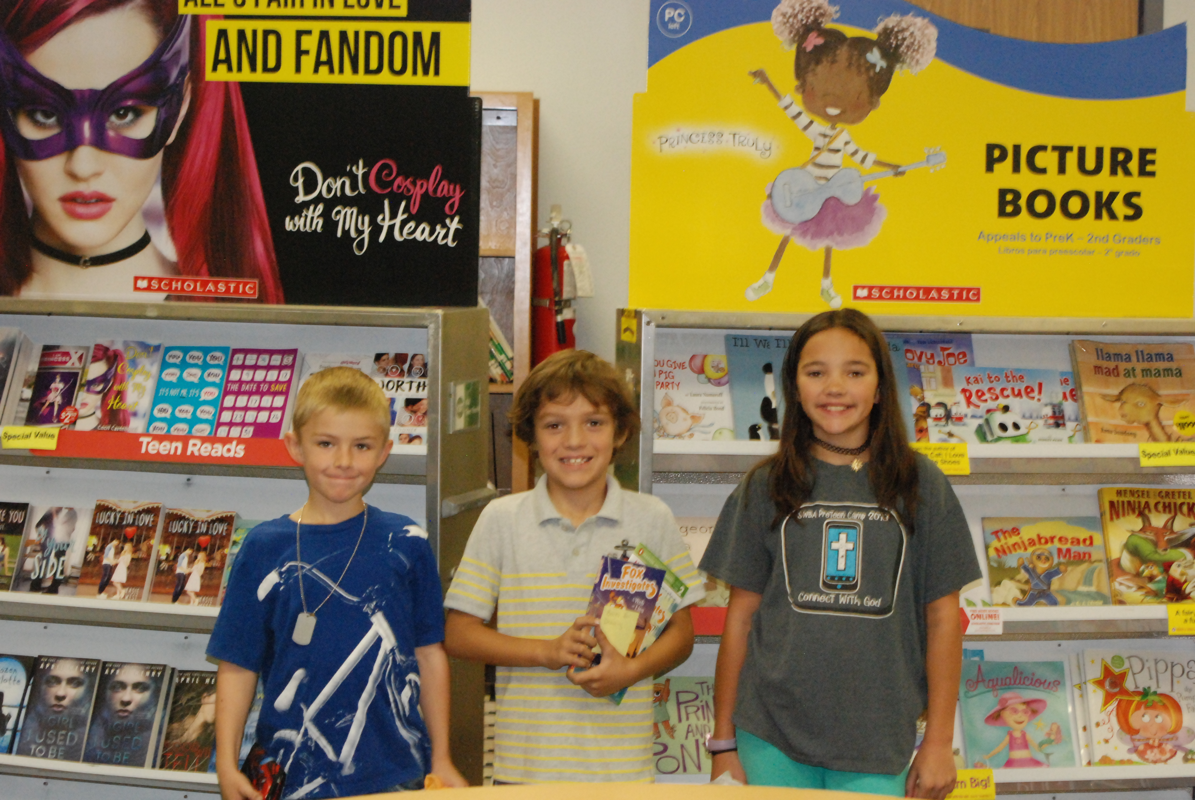 3 students with new books from Scholastic book fair