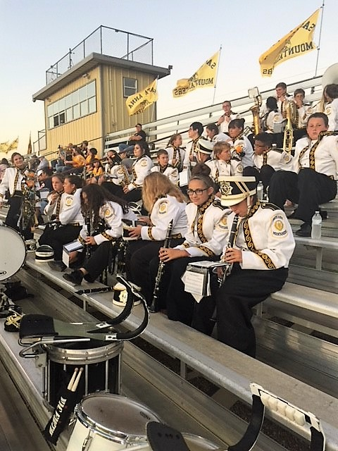 band in uniforms in stands at game